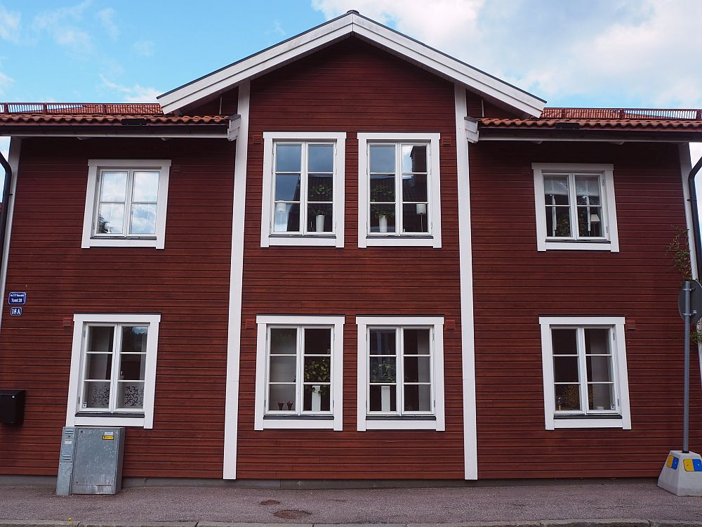 The house is 2 stries high, painted deep red with white around the windows and roof, and two white strips down around the central two windows. Four windows on each of 2 floors.