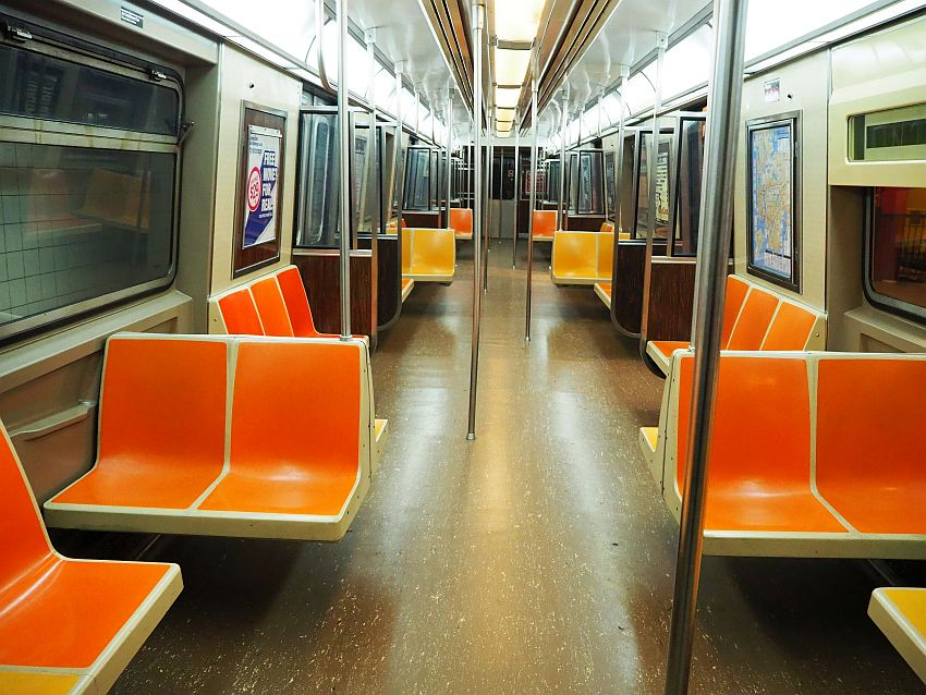 Looking down the length of a subway car. Harsh lighting, chairs of molded orange or yellow plastic along the walls or perpendicular to them. Here and there a floor to ceiling metal pole.