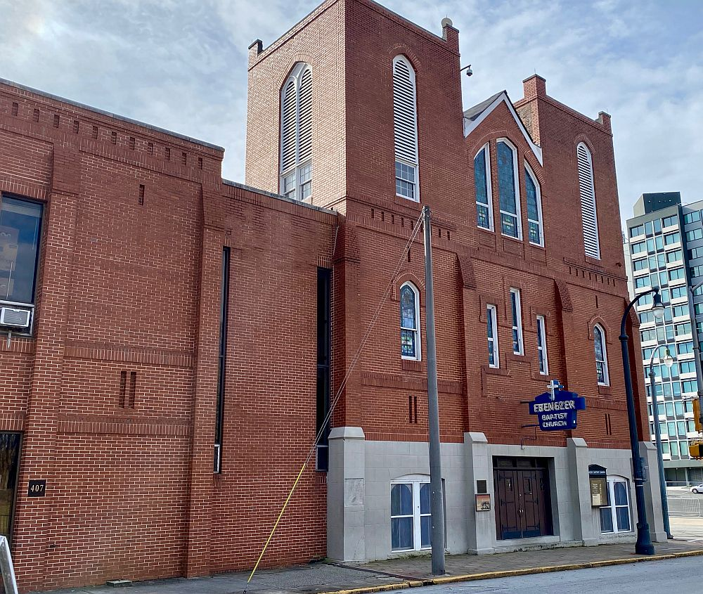 A view of the Ebenezer Baptist Church: a modest, 3-story brick building with arched windows edged in white paint.