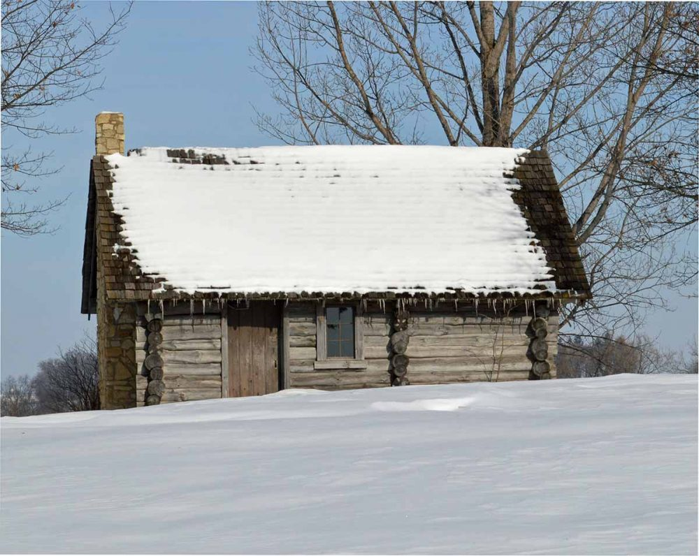 A simple log cabin with a slanted roof is one of the Little House on the Prairie locations. The roof has quite a bit of snow on it, with icicles hanging off the eaves and the field in front of the house is also covered in smooth snow. A large bare tree shows from behind the house.