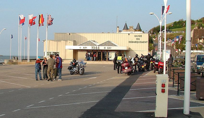"""The front of the Musee du Debarquement: a simple low building without windows, off white, flat roof, with the words """"6 juin 1944 D-Day"""" above the entrance. In the mostly empty parking lot in front are several motorcycles with their riders standing around them and talking. Beside the building are a number of flagpoles with various countries' flags flying."""