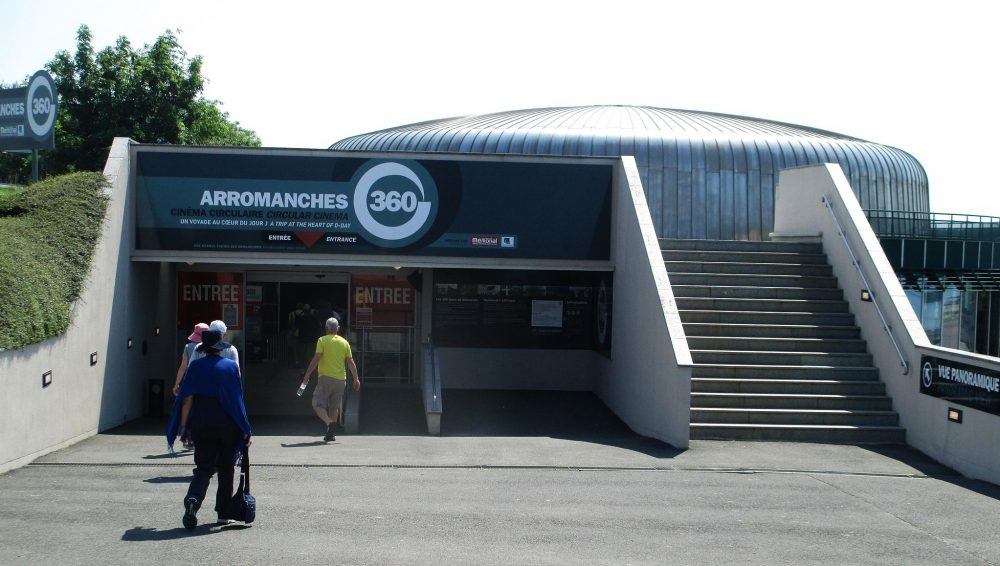 The entrance is low, and looks to be built into the side of a low hill. To the right of the entrance is a stairway up one flight to the roof of the entrance. Behind, part of the cinema itself is visible: a round low cylindrical structure. Above the entrance door: Arromanches 360.