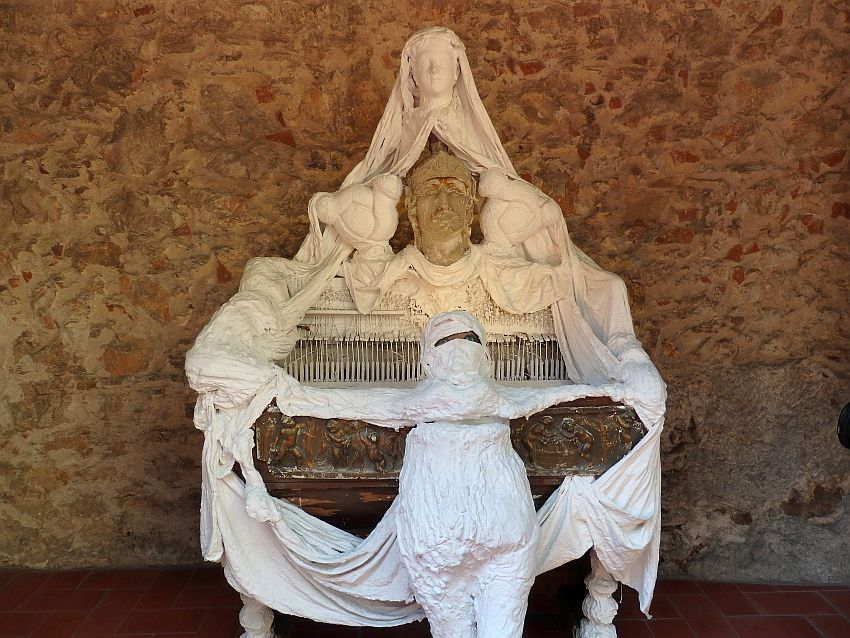Something like a harpsichord or old piano is draped with cloth and papier mache figures, all in white. In the center, on top of the piano, a persons head. Above that, another person's head. In front of the piano, a somewhat human shape made of white plaster or papier mache, with a head almost completely wrapped in except for a slit where two eyes peer out.