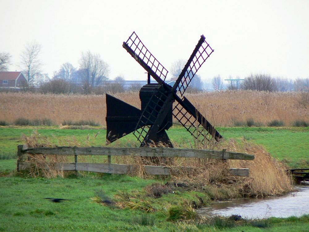 A small windmill, perhaps twice the height of a person. It looks like it's made entirely of wood, and the four vanes do not have sails on them so it is probably not turning. It stands next to a ditch in a green grassy field.