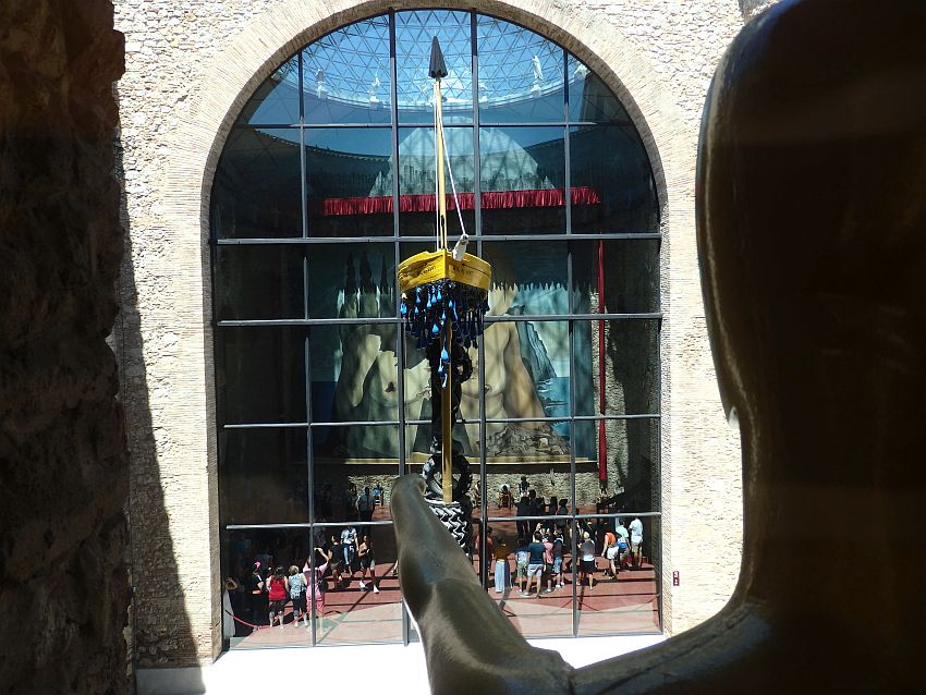 On the right is the back view of a head, with an arm sticking out straight ahead. It seems to point at the boat standing on top of a pole. Behind that is a large arched window. People are visible inside the building at the bottom of the multi-story window, mostly looking up at the huge multi-story painting on the far wall, which shows a naked torso.