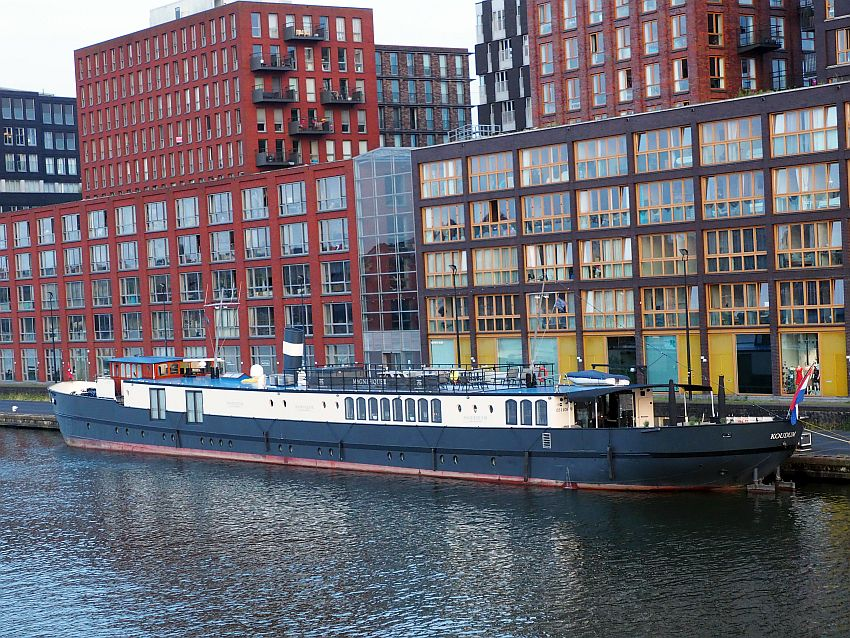 The boat is tied to the riverside and is long and low. The hull is black with a row of portholes just above the water line. Above that is painted white, and has bigger windows here and there. Behind the boat are tall buildings with lots of windows.