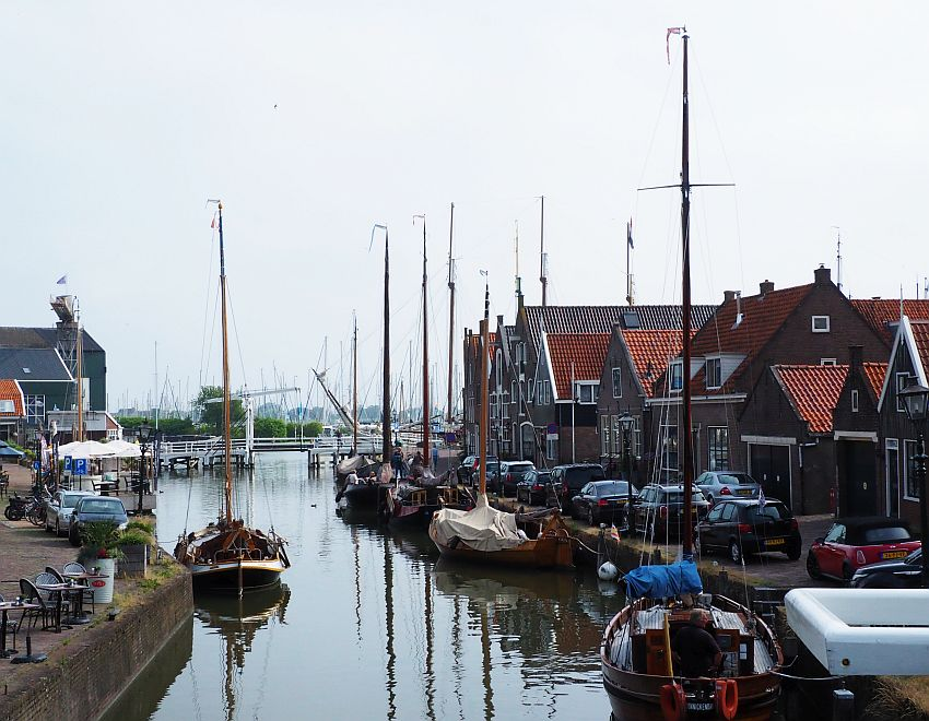 A canal with a row of houses of various shapes and sizes along the side and a row of wooden sailboats moored along the sides of the canal.