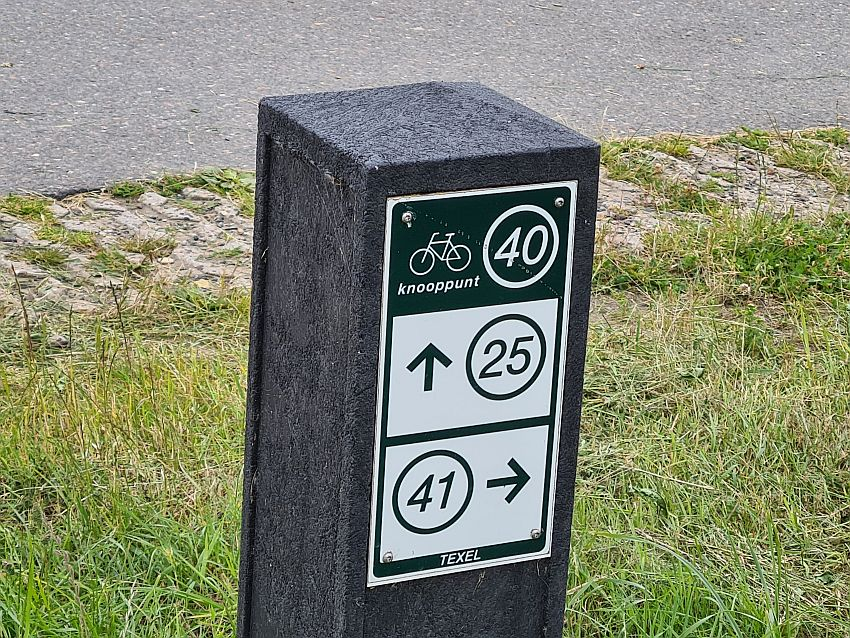 A short wooden pole with a sign attached to it. At the top, a line drawing of a bicycle next to the number 40 in a circle. Below, the numbers 25 and 41, each in a circle with an arrow next to it.