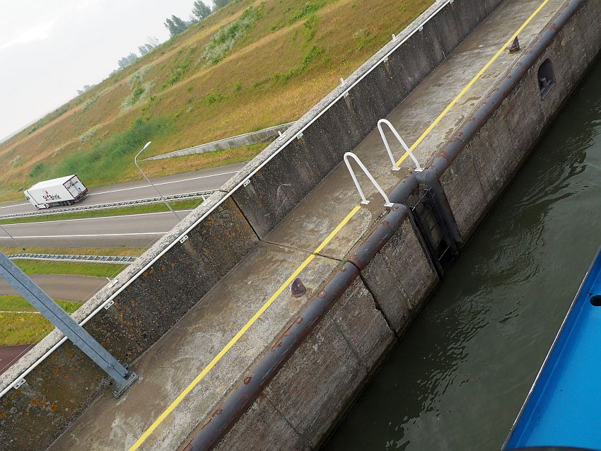 The picture is taken on the diagonal, so a bit of the boat can be seen in the bottom right corner, a strip of water beside it, then a concrete wall, then, at the top left corner, a street extends to the left, with one cargo truck visible.