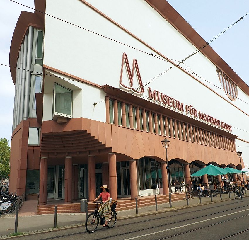 A large building on a triangular lot so the part shown has a sharp corner at the left of the photo. The building is dark red on the lower floors with arches and plain pillars and white above with no ornamentation. A cafe on the sidewalk with green umbrellas over the tables. A woman bicycles by.
