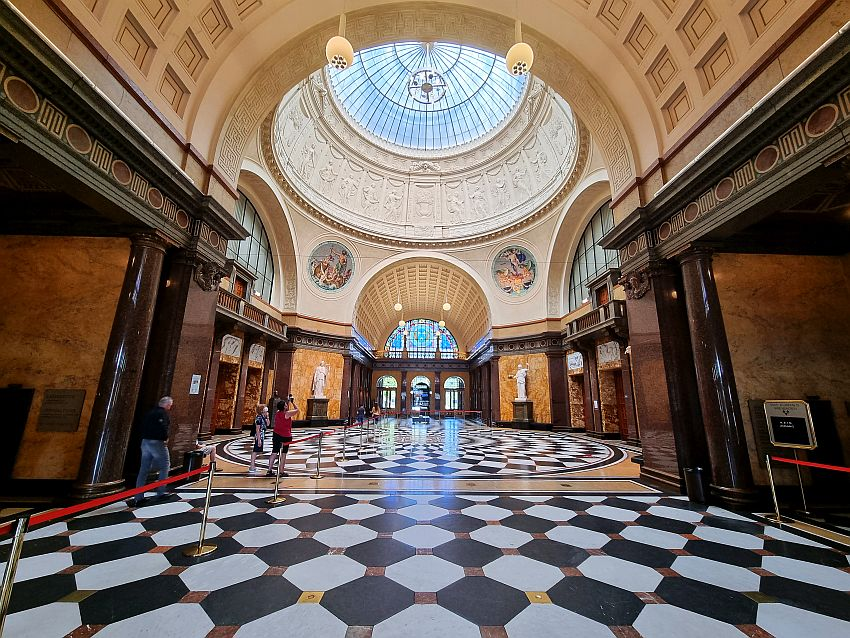 A long hallway, straight sided except the middle portion, which is round, with rounded sides and a large dome above it. Part of the dome is visible in the view and shows decorative detail around the bottom of the dome and the top of the dome is panes of glass. The floor is marble placed in a chessboard pattern. The walls sport pillars of marble at each doorway. Many historic spa towns had such ornate gathering places.