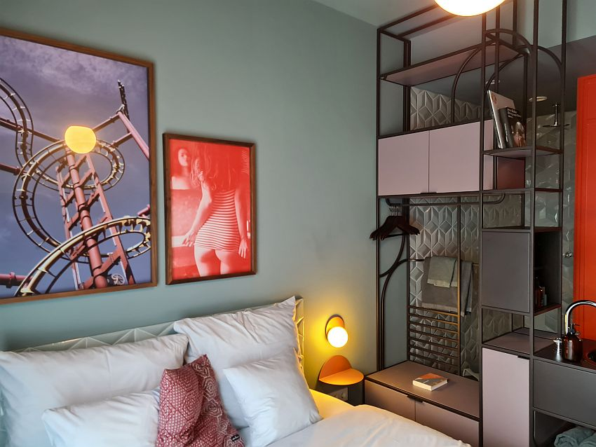 This view shows the top end of the bed with several pillows against the backboard. The wall above the bed has two framed photos: one shows part of a metal roller coaster track. The other shows a woman from the back looking in the mirror, wearing a tight tee-shirt and no underpants. A wall unit along the side of the bed has open shelves and a couple closed cupboards, as well as a rod and some hangars. Part of a sink is also visible in the wall unit. Behind the wall unit (as seen through the wall unit), the wall is patterned tile, white but with a profile.