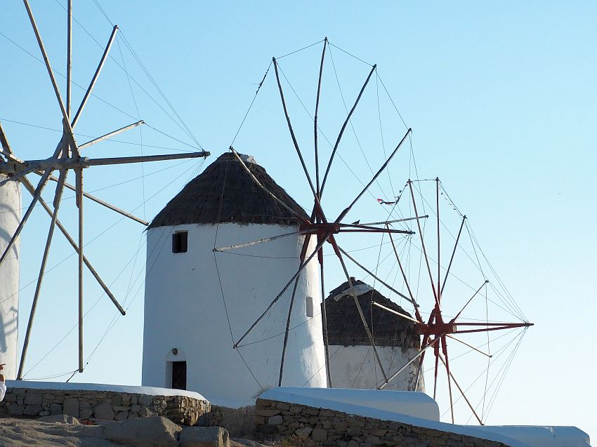 3 white, cylindrical windmills with pointed straw roofs. what used to be the windmill part is just an array of wooden poles in a circle.