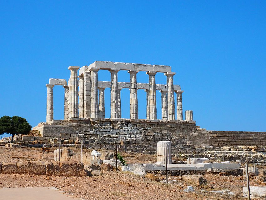 The temple stands on a high stone base against a blue sky. On the base is a square of lined-up columns, some of them holding up cross-stones as well. It is all white marble. Some additional pices lie on the ground in the foreground.