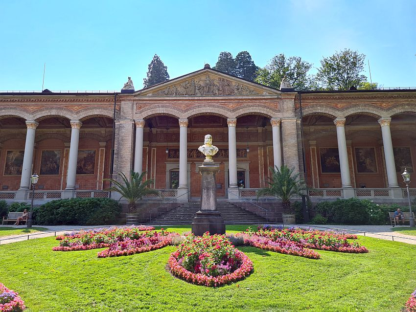 A neo-classical portico fronts the building: a row of corinthian columns supporting arches and a deep hallway along the front for strolling. The four center pillars support a pediment with a bas-rief inside it. In front is a pedestal with a bust on it of Kaiser Wilhelm I. Neat flower beds radiate out from the foot of the pedestal.