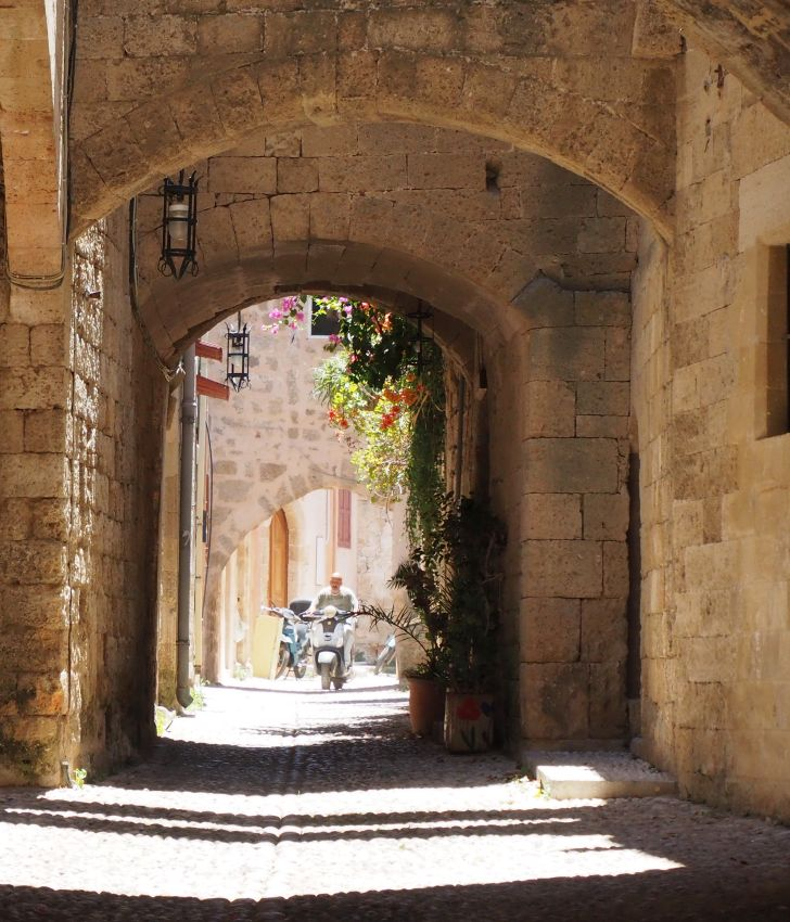 Looking along a narrow street: stone walls of buildings on both sides, arches over the street in the nearer part, then sun shining beyond that. The ground is cobbled. A motorcycle approaches.