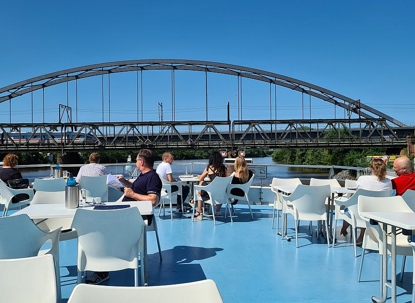 The deck of the boat is blue matching the color of the sky above. White tables with white chairs are set around the deck, and people sit at some of them. Across the photo in the middle, and seemingly at the same height as the deck, is an iron railway bridge. A train can be seen crossing it.