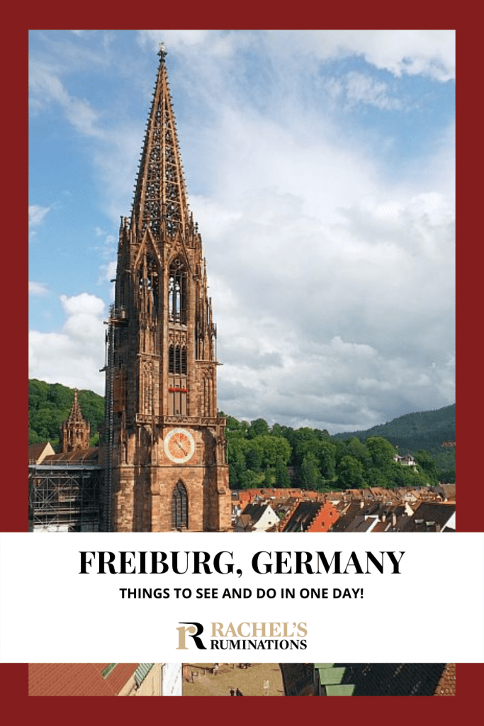 Text: Freiburg, Germany: Things to see and do in one day! (and the Rachel's Ruminations logo). Image: the tower of Freiburg Cathedral, with just the roofs of the town visible to the right and a tree-covered hill behind under a partly cloudy sky.
