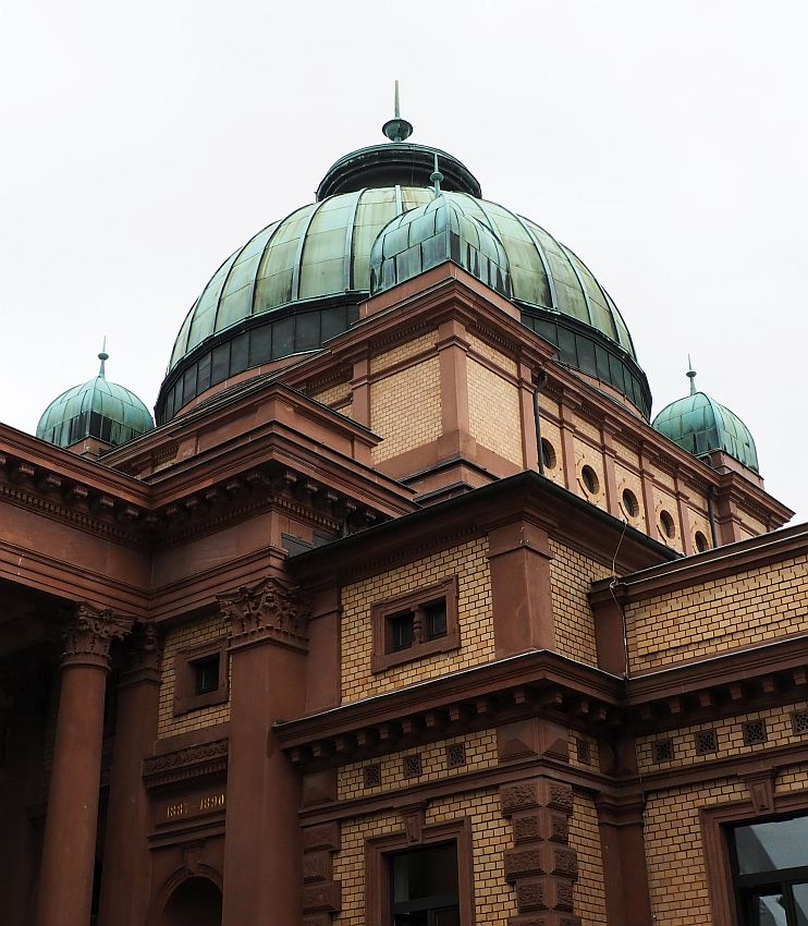 The walls are a yellowish brick with dark red stone edges and columns. The domes above are green copper: one large central dome and 3 smaller ones visible in this photo.