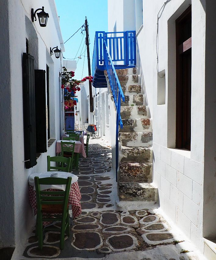 Looking along a very narrow street. On the left, a few small tables against the left wall, each with two chairs against the wall as well. On the right, a stairway up, with the railing painted bright blue, and also the landing at the top of the stairs. All the walls along the street are painted bright white. The ground is flat stones, with white painted around the edge of each. There is just enough space for one person to pass between the tables and the stairway.