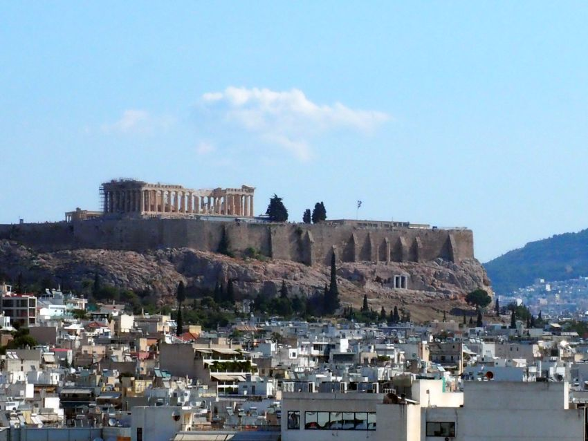 Looking at the Acropolis from a medium height, so that the whole Parthenon can be seen from the side, with it's intact walls of pillars. Below that, the side of the hill is surrounded by stone walls, and below the walls, cliffs. Below the cliffs is the jumble of city buildings.