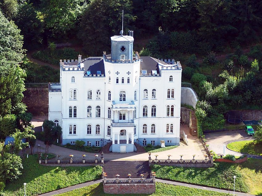 A square block of a building in Bad Ems, Germany, seen from a higher elevation: white, with 4-5 stories, more or less symmetrical. Along the edges of the roof are small crenellations and in the center is a squat round grey tower.