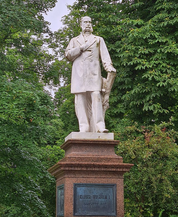 A standing figure on a pedestal. He stands with one hand leaning on a cut-off tree trunk, the other stuck into the chest of his jacket. The jacket is long, to above the knees, and buttoned closed. He has an unusual beard: the sideburns are thick and long to the corners of his mouth, but the chin is clean-shaven. The mustache curls up at each end.