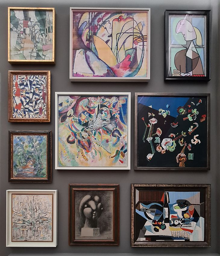The paintings are set very close together on the wall, all in frames. The are all abstract, or semi-abstract.