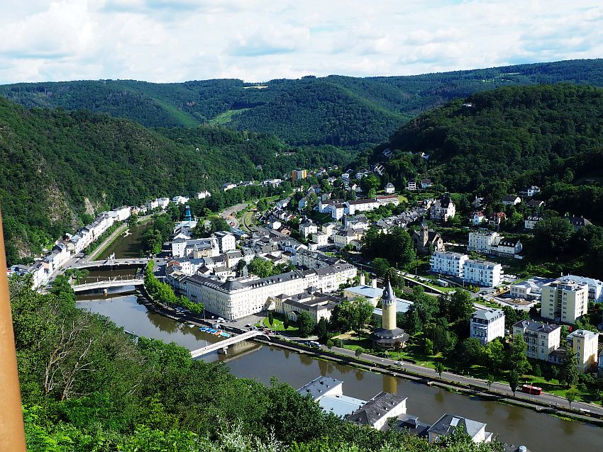Looking down on Bad Ems, Germany, the river curves out of sight between the surrounding hills. Three bridges cross it. A scattering of buildings along the far bank and behind where the land is fairly flat. On the near side a single row of buildings backed by a steep hill.