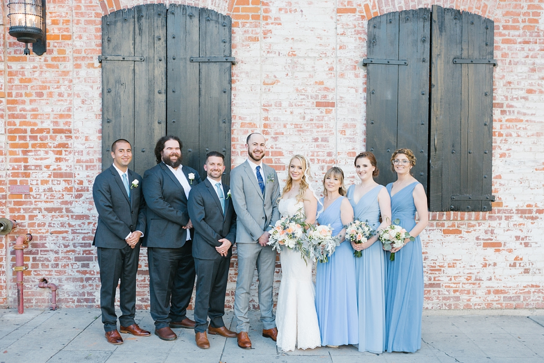 the wedding party stands outside carondelet house for a photo