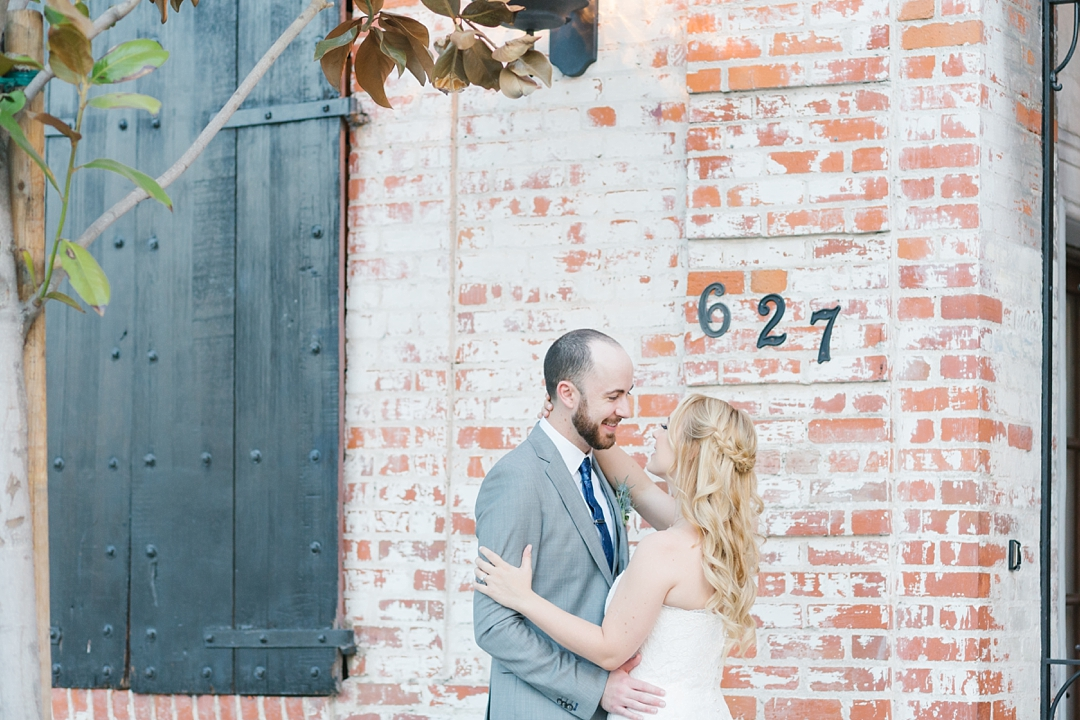 bride and groom in front of brick walled venue in los angeles