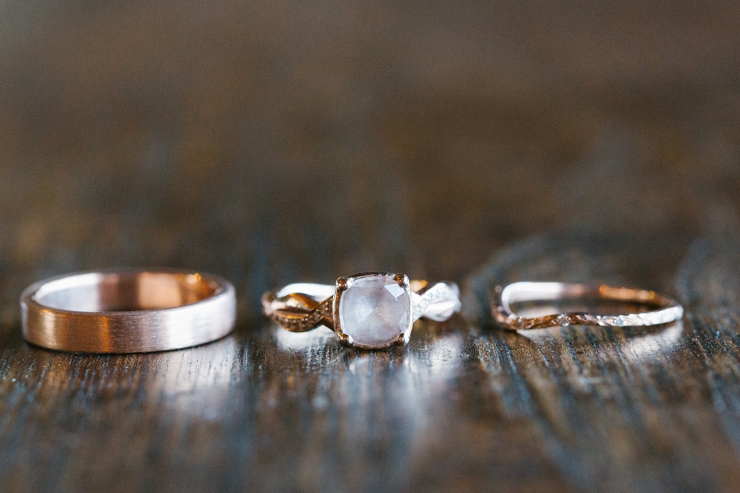 rose gold wedding rings on wood table