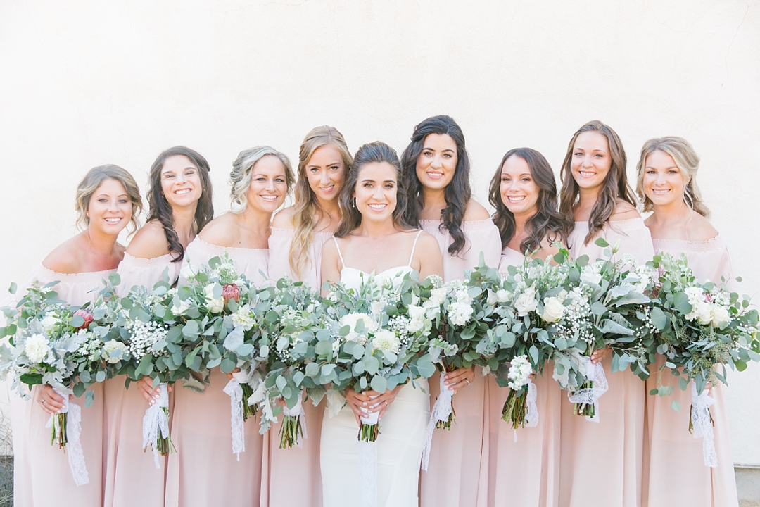 bridesmaids in soft pink dresses against white wall