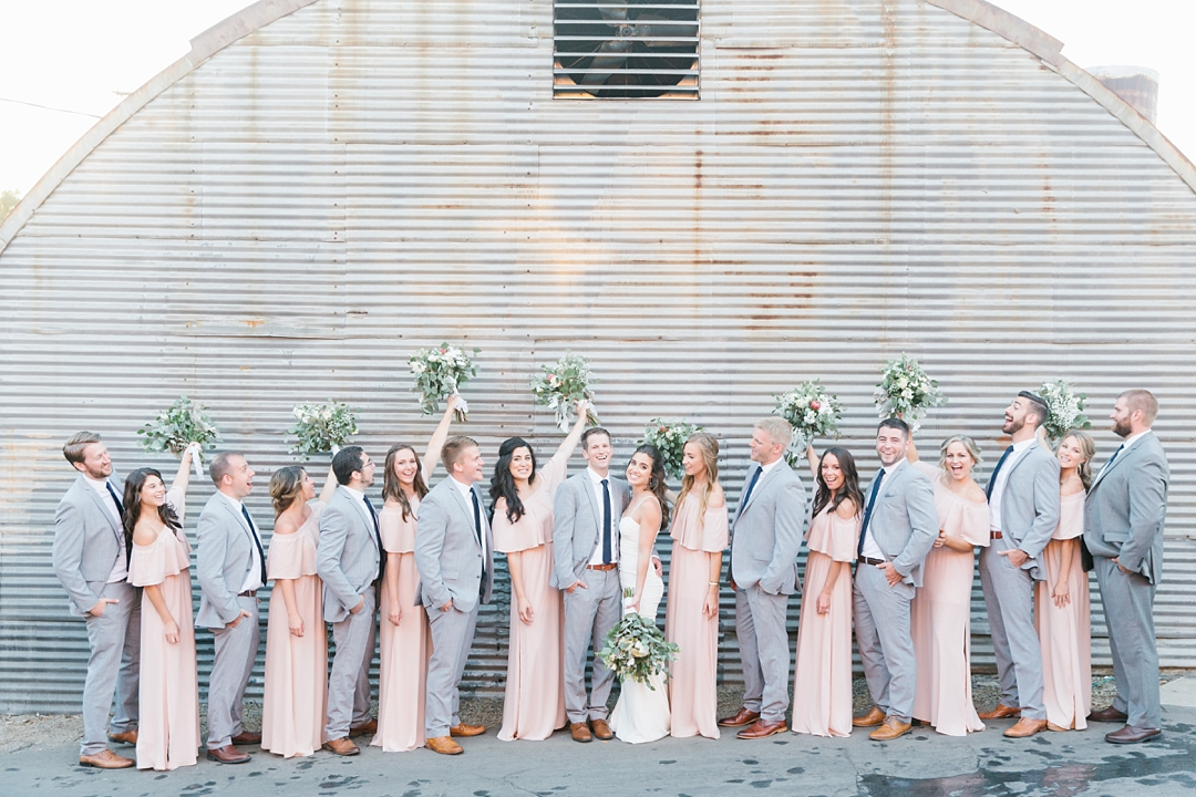 large bridal party against metal wall outside smoky hollow studios