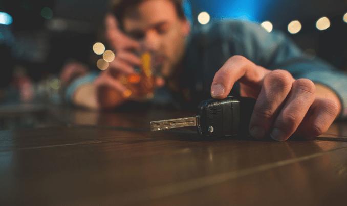 drunk man drinking with car keys in hand