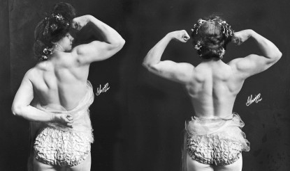 Victorian Strongwomen Charmion shows her bare upper back while flexing biceps.