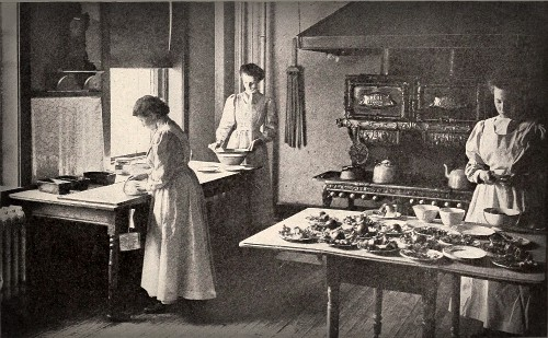 Black and White photo of three women in kitchen ofThe Boston Cooking School Magazine of Culinary Science and Domestic Economics (1908). Image: Wikipedia.