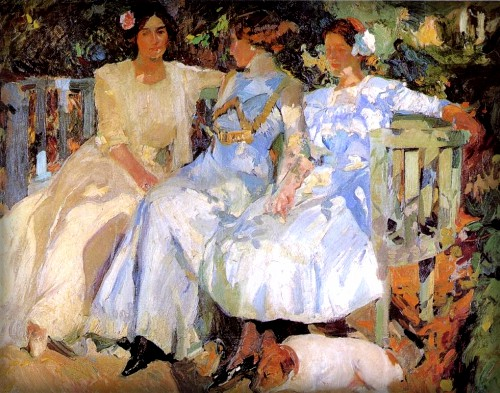 Three Women In long white dresses in 101- sit in dappled sunlight on a bench in the garden.