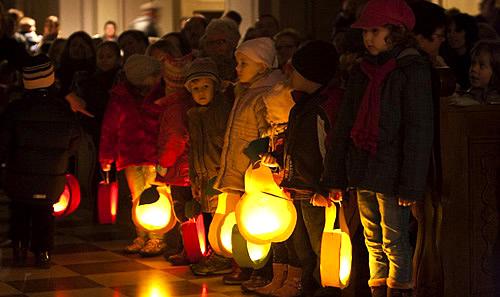 European Lantern Parade children holding glowing lanterns in darkness. Image: GermanCulture.com.