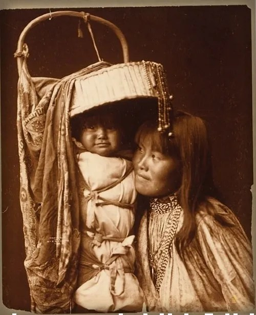 Apache Woman Bust only With Smiling Baby In Cradleboard, slightly above her face 1903 by Edward Curtis. Image: National Archives.