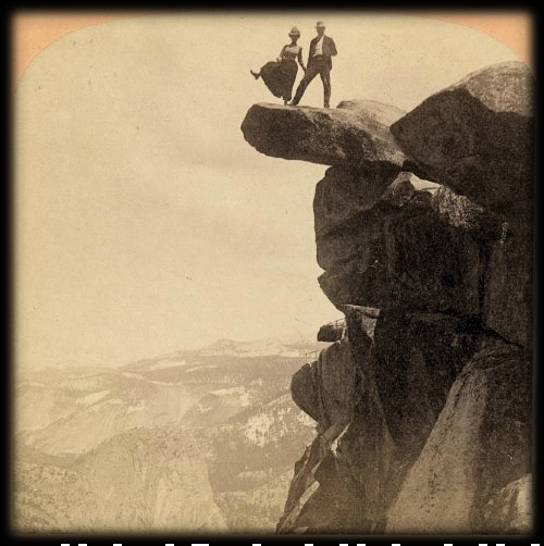 Glacier Point 1890s photo taken from far away ofof Man and woman standing at edge of rock extending from top of cliff; woman is raising her right leg as though to step off with valley below.