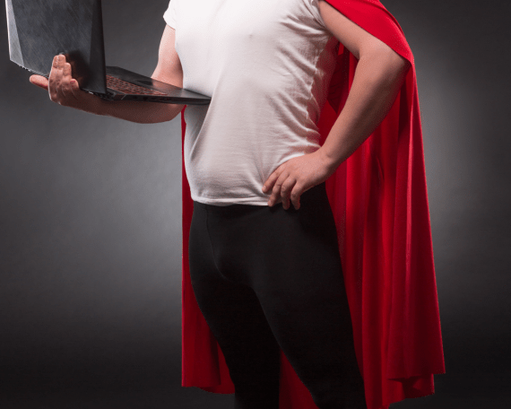IT Ops man in a cape, holding a laptop