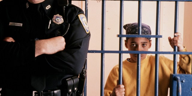 YOUNG BLACK BOY IN JAIL BEHIND POLICEMAN