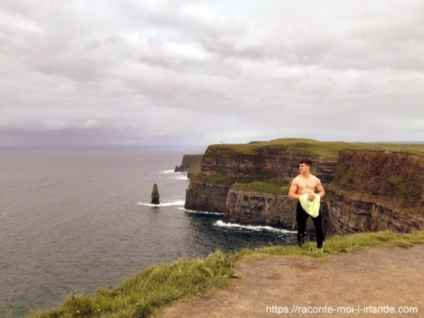 Jeune homme en haut des falaises de moher irlande