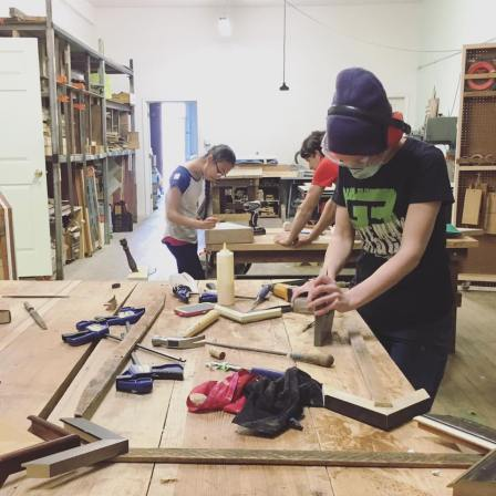 Women work with wood and associated tools in a brightly lit workshop.