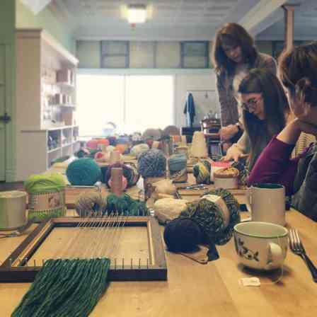 Women work with colorful yarn and a loom over hot tea.