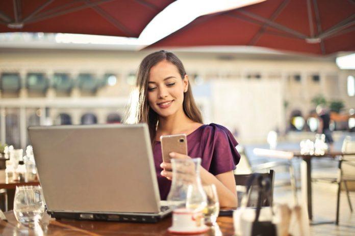 """Equipes de marketing que acompanham todas as tendências de SEO, precisam reformular sites para atenderem aos padrões do Mobile-First Foto por bruce mars em <a href=""""https://www.pexels.com/photo/woman-wearing-purple-shirt-holding-smartphone-white-sitting-on-chair-826349/"""" rel=""""nofollow"""">Pexels.com</a>"""