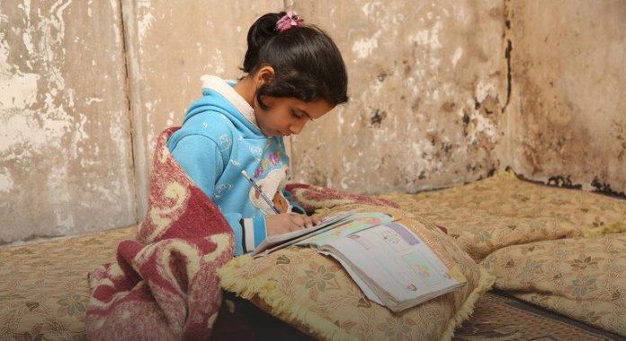 Criança sentada no chão escreve em um livro de estudo, em retrato da pobreza. Foto: ONU