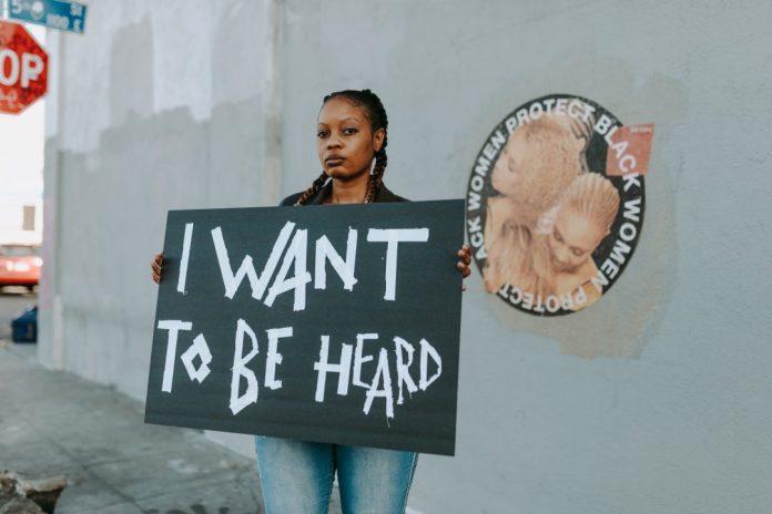 Mulher protesta na rua, reivindicando ser ouvida pela sociedade.