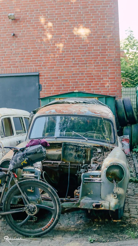 Altes Auto mit angelehntem Fahrrad